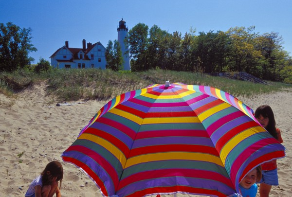 BEACHGOERS UNDER AN UMBRELLA AT THE POINT IROQUOIS LIGHTHOUSE  NEAR BRIMLEY, MICHIGAN.
